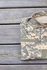 Neatly folded military jacket. Wooden desk table background.