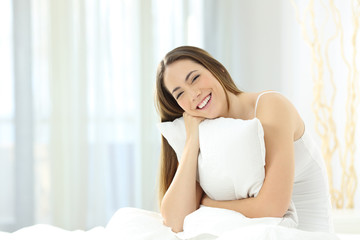 Candid girl embracing a pillow looking at camera in the bed