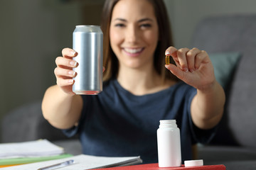 Student showing energy drink and vitamin supplement pills