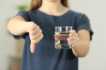 Woman holding a water glass with thumbs down