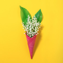 Ice cream cone with lily of the valley flowers on a yellow background. Minimal spring concept. Flat lay