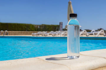a bottle of water against a pool background as a symbol of a lack of water in the body in the summer