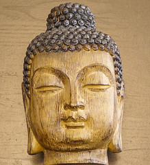 Wooden Carved Buddist Head with wood grain background