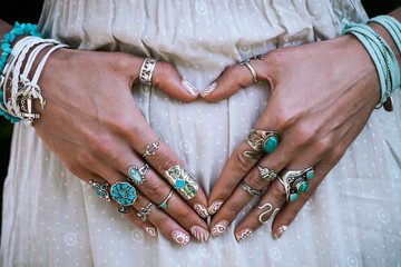 closeup of young woman hands in heart shape with lot of boho style jewrly, rings and bracelets outdoor