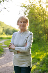 Elderly woman in a sunny park. How to be happy in old age