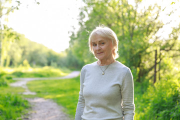 Thoughtful elderly woman in a sunny park. How to survive the death of a loved one, illness, be happy in old age