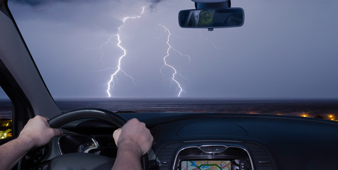 Driving a car towards a lightning storm over the sea