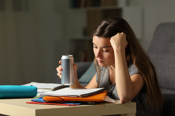 Student memorizing holding and energy drink in the night
