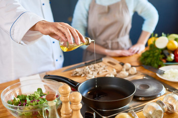 Photo sur Plexiglas Cuisine Close-up of male chef pouring oil into the pan
