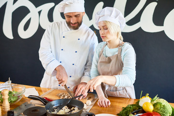 Chef and his assistant preparing dish together