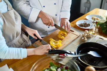 Close-up of chef and his assistant preparing salad together