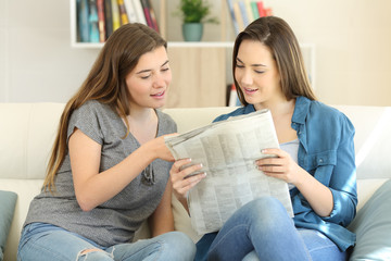 Two friends reading newspaper news