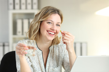 Happy office worker showing a vitamin supplement pill