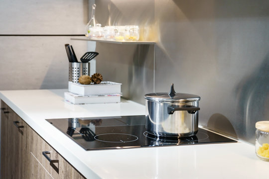 Metal Pot on induction hob in modern kitchen. modern kitchen pot cooking induction electrical stove hob concept