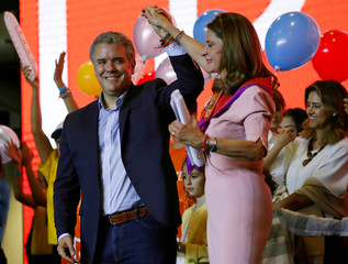 Right wing presidential candidate Ivan Duque holds the hand of his vice-presidential candidate Marta Lucia Ramirez in Bogota