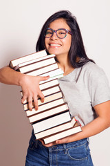 Latin nerdy girl holding in hands a pile of books. Indoors, over a white wall.