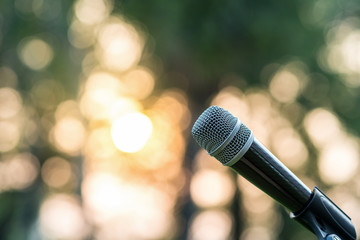 Microphone on the stage over the Abstract blurred photo of green tree with sunset light background, Musical and presentation concept