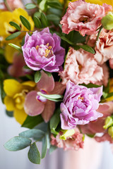 Spring bouquet of flowers with orchids, tulips and eustoma. Pink yellow flower arrangement