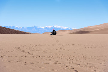 Woman hiker sitting on sand at Great Sand Dunes National Park, Colorado