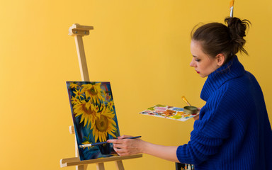 Girl artist paints sunflowers oil paints on canvas. She is wearing blue sweater. Woman is holding brush and palette with paints.