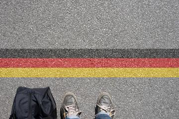 Ein Mann mit einem Koffer steht an der Grenze zu Deutschland