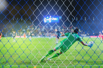 Goalkeeper and players during penalty shoot in soccer match. select focus at the net