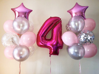 a gentle composition of balloons of pink and silver colors, as well as a bright pink star and a large four colors of fuchsia