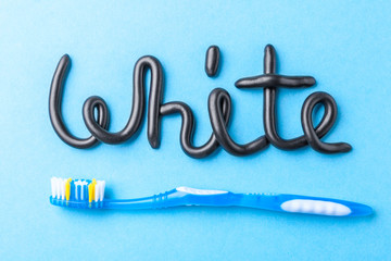 Black toothpaste from charcoal for white teeth. Word WHITE from  black toothpaste and  toothbrush on  blue background.