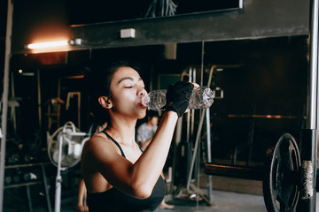 Asian young woman drinking water in the gym.