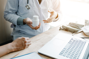 Confident doctor man holding a pill bottle talking with senior patient at office room.