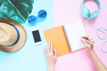 Creative flat lay woman's hands with notebook and smartphone, hat, sunglasses and headphones on pastel color background, Summer vacation concept