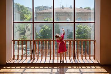 little russian ballerina girl in traditional dress barre exercise near window