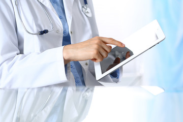 Woman doctor using tablet computer while sitting. Reflecting glass table is a working place of physician. Healthcare, insurance and medicine concept
