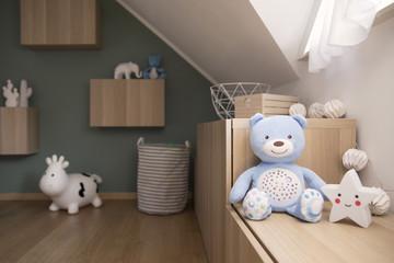 Stylish scandinavian newborn baby room with toys, teddy bear, mock up photo frame. Modern green background wall.