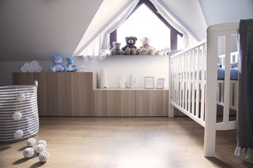 Modern scandinavian nursery interior with toys, teddy bears, baby cot and cotton bowls lamps. Sunny and bright room.