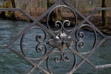 close-up of the black iron ornaments of a bridge's handrail