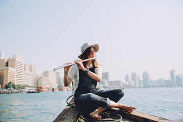 oung beautiful woman sitting at boat and playing the flute