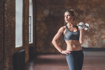 Young sporty woman with a dumbbell in training