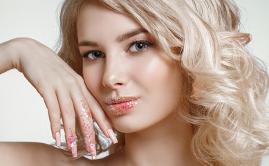 close-up portrait of beautiful curly blondy woman with perfect art make-up, trendy frosted nail design with glitter. Wind in her hair