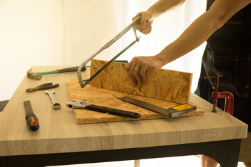Carpenter cutting a board with a handsaw on the table.