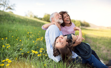 Senior couple with grandaughter outside in spring nature, relaxing on the grass.