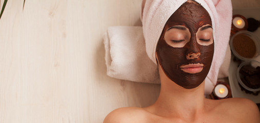 Chocolate Luxury Spa. Facial Mask. Spa therapy for young woman with cosmetic mask at beauty salon. Day spa treatment