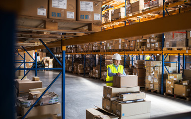 A senior woman warehouse worker or supervisor controlling stock.
