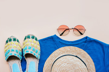 Summer fashion flatlay with gradient round sunglasses, straw hat, espadrille sandals and t-shirt on the beige background. Perfect beach set for holidays on the sea. Marina style.