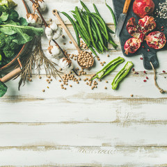 Winter vegetarian, vegan food cooking ingredients. Flat-lay of vegetables, fruit, beans, cereals, kitchen utencil, dried flowers, olive oil over white wooden background, top view, copy space, square