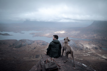 Man with dog sitting on a rock