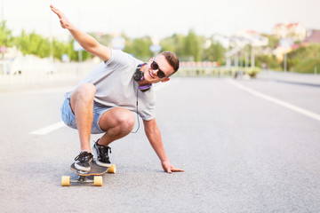 Skateboarder in sunglasses rides longboard on asphalt road in the city, low position trick ride