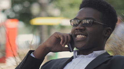 Handsome african american man laughs and talks on his cell phone