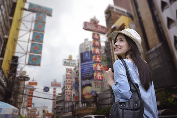 Young asian woman traveler with a backpack on her shoulder and travel hat walking on footpath over China town, Bangkok, Thailand, Travel holiday relaxation concept