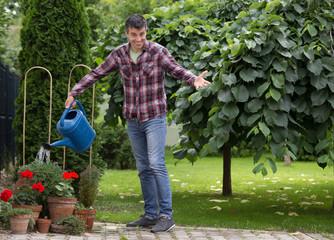 Gardener with watering can in garden